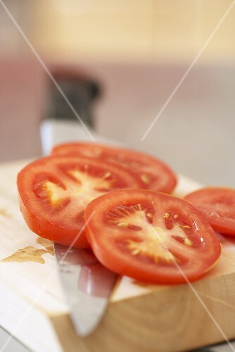 Tomato slices on chopping board with knife