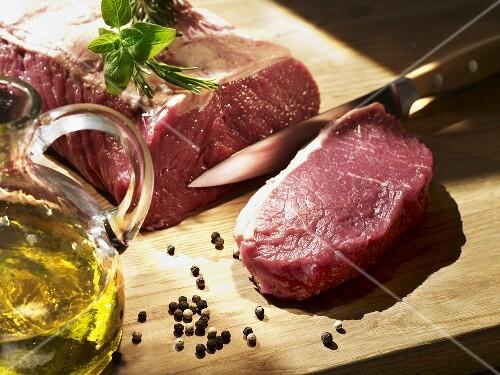 Beef sirloin with a slice cut, oil, herbs, peppercorns