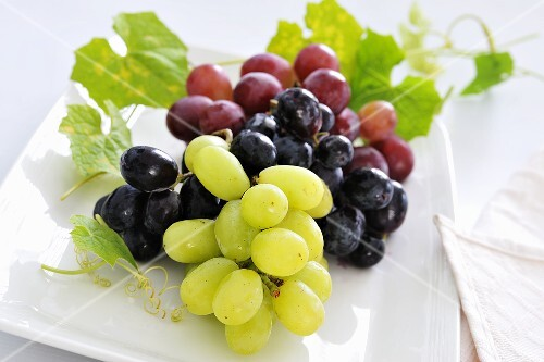 Green and red grapes with leaves on plate