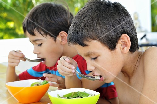 Two children eating soup