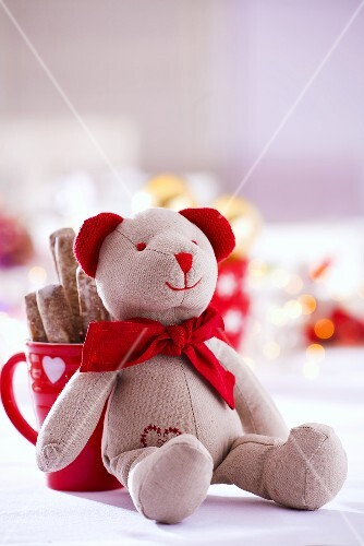 A teddy bear leaning against a cup of biscuits