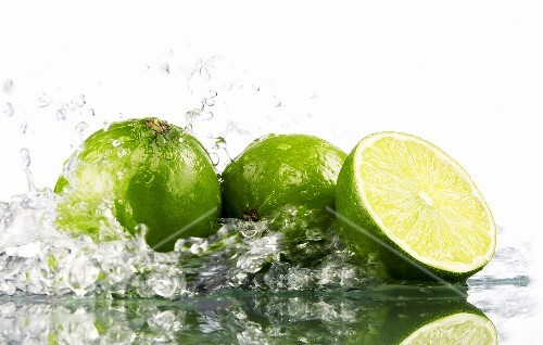 Limes with splashing water