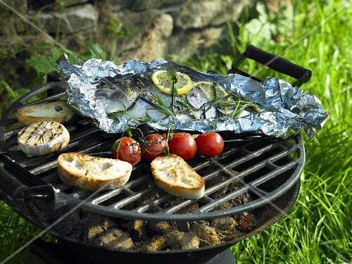 Foil-wrapped bream on a barbeque