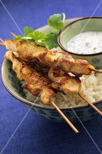Chicken kebabs with rice and a yogurt sauce