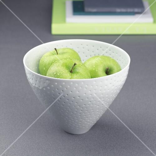 Three apples in a ceramic bowl