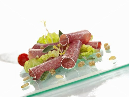 Salami rolls with salad leaves and pine nuts
