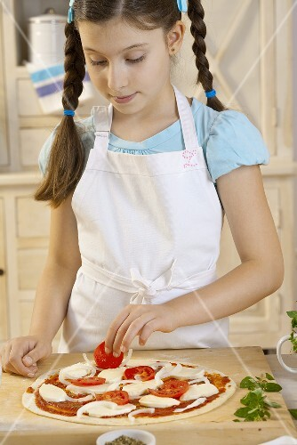 Girl putting tomatoes on pizza