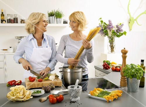 Women having a laugh while cooking spaghetti