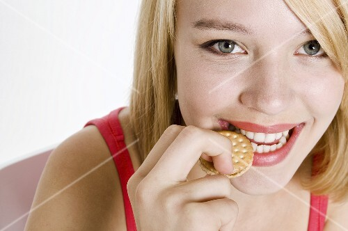 Young woman biting into a mini sandwich biscuit
