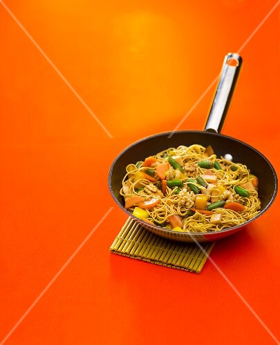 Vegetable chop suey with noodles and walnuts in frying pan