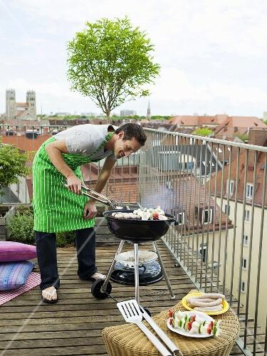 Man preparing barbecue on balcony