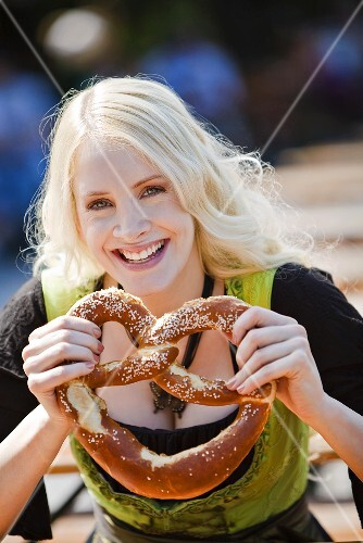 Germany, Bavaria, Munich, English Garden, Young woman holding soft pretzel, close-up