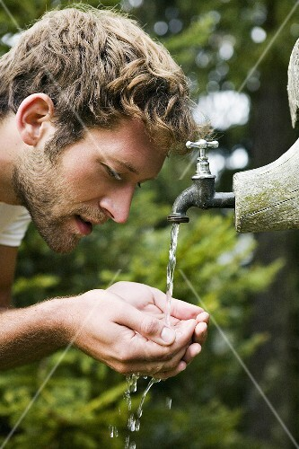 Young man cupping water from fountain, close-up, side view