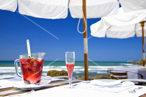 Sangria with berries in jug & sparkling wine glass on table by sea
