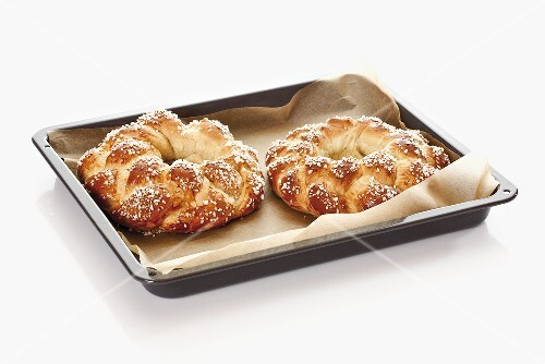 Bread wreaths with sugar on baking tray