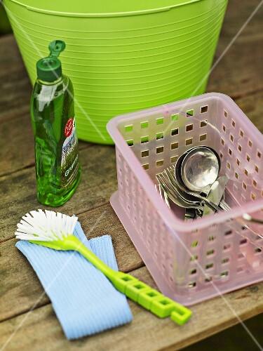 Besteck, Spülmittel, Bürste und Plastikwanne auf Holztisch