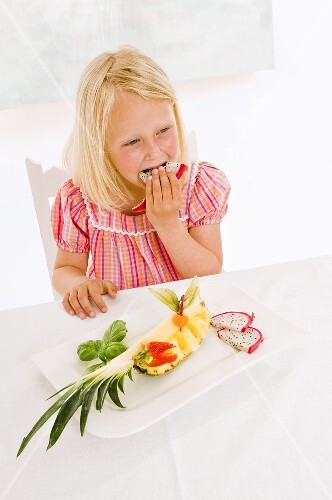 Girl eating pitahaya from plate of fruit