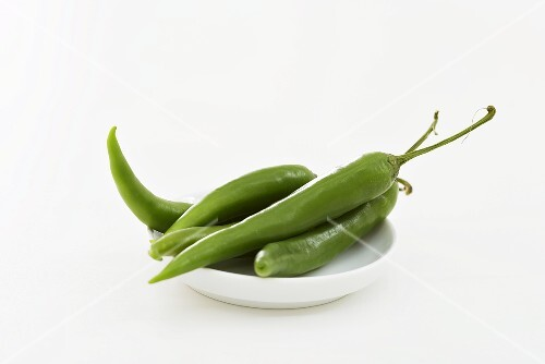 Several green chillies on plate