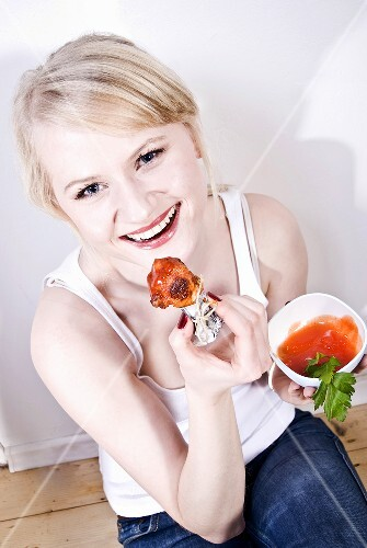 Woman eating chicken wings with sauce