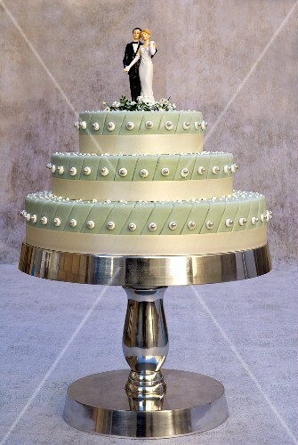 Three-tiered wedding cake with bride and groom cake toppers