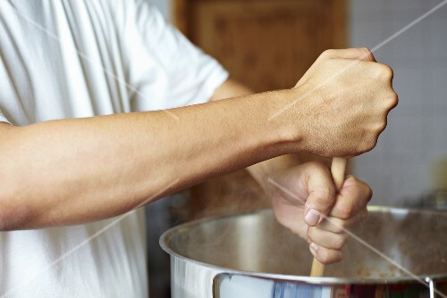 Chef stirring a pan with a wooden spoon