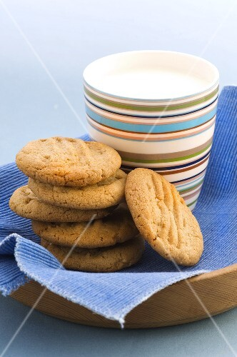 Peanut biscuits, stacked, with beaker of milk