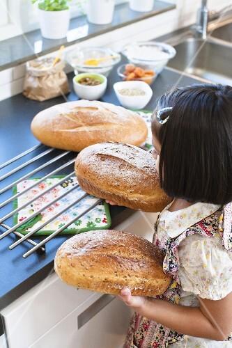 Girl holding freshly baked bread in the kitchen