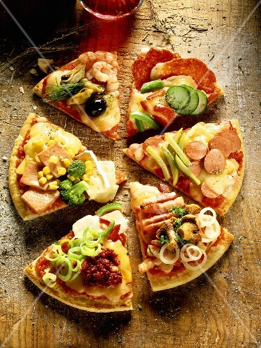 Pieces of pizza with different toppings, on wooden background