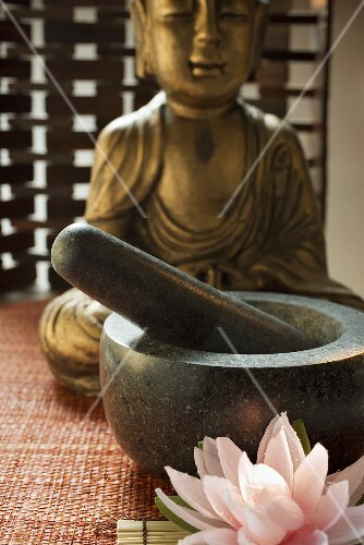 Mörser mit Stössel vor Buddhastatue (Asien)