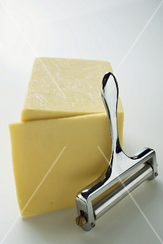 Semi-hard cheese with a slice cut and a cheese cutter