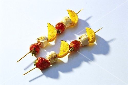 Two sweet strawberry and orange kebabs with marshmallows