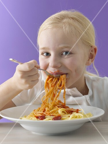 A blonde girl eating spaghetti with tomato sauce