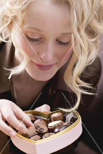 Young woman eating chocolates