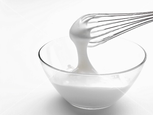 Whipped cream in bowl with whisk