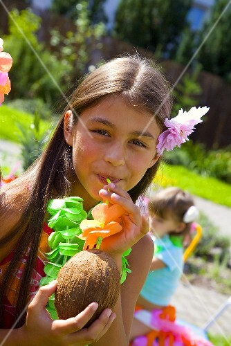 Girl drinking coconut milk out of coconut at children's party