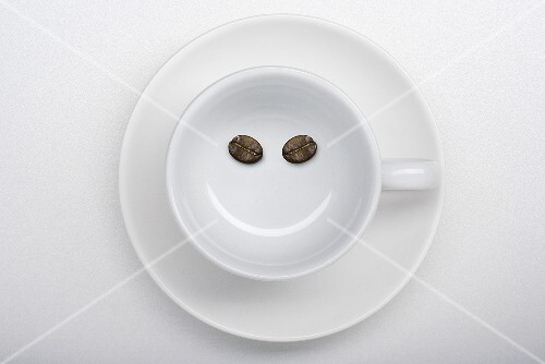 A coffee cup with two coffee beans making a smiley face