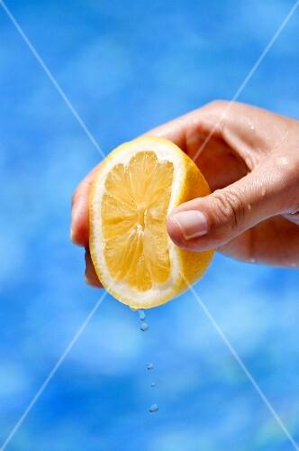 A hand squeezing a lemon