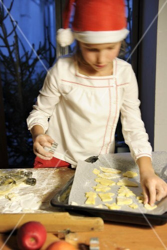 A girl placing cut out biscuits onto a baking tray