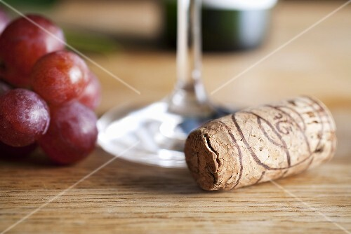 Grapes and a cork next to a wine glass
