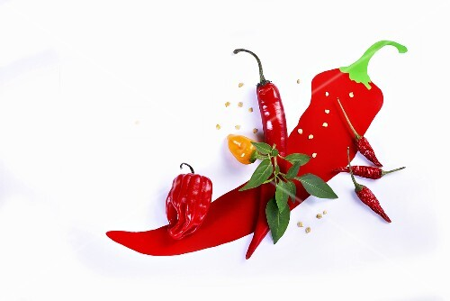 Various fresh chilli peppers on a picture of a chilli pepper