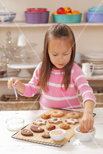 A girl decorating biscuits with sugar pearls