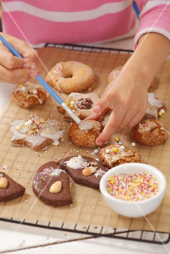 A girl decorating biscuits with icing sugar