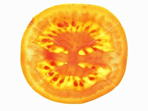 A tomato slice, lit from behind