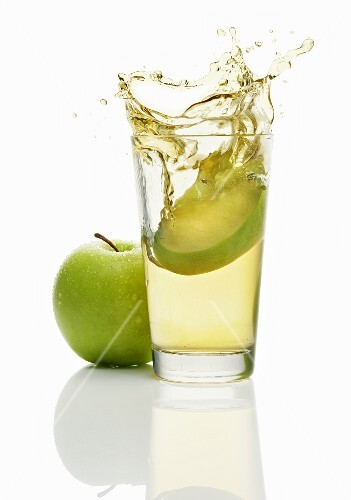 Wedge of apple falling into a glass of apple juice
