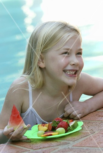 Small girl with fresh fruit at the pool