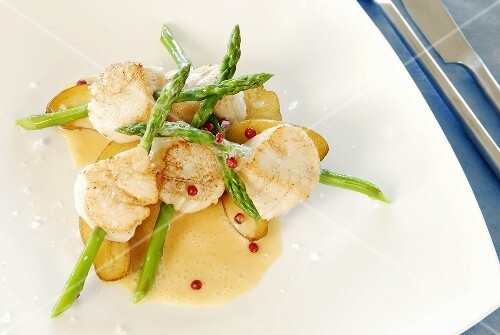 Scallops speared on asparagus with butter sauce