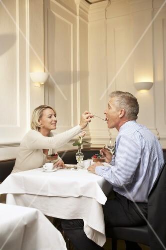 Mature couple enjoying dessert in a restaurant