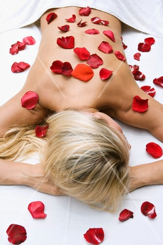 Prone, blonde woman with rose petals scattered on skin