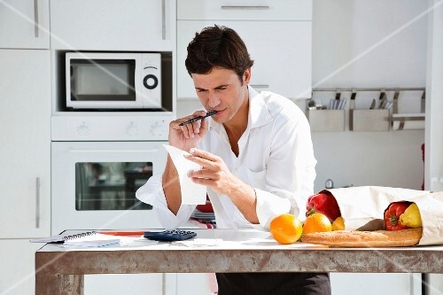 Man in kitchen with shopping calculating household budget