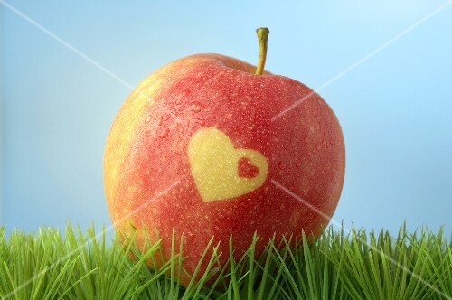 Red apple with heart in grass (blue background)